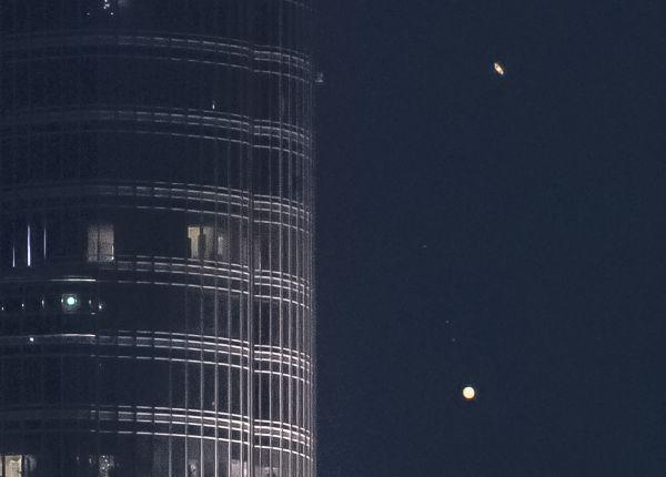 The rings of Saturn glide above Jupiter as the two planets pass near Burj Khalifa, the world's tallest building.