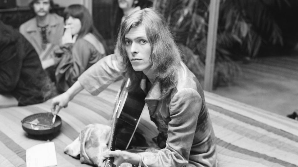 David Bowie jams at a party at lawyer Paul Figen's house in January 1971. (Photo by Earl Leaf/Michael Ochs Archives/Getty Images)