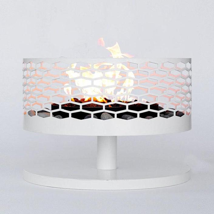 """Take your backyard patio to the next level with a full-on outdoor fireplace. This midcentury-modern design is surrounded by a retro patterned fire screen and cheerful base. $1150, 2Modern. <a href=""""https://www.2modern.com/products/solfire-hex-outdoor-fireplace?variant=25101088521"""" rel=""""nofollow noopener"""" target=""""_blank"""" data-ylk=""""slk:Get it now!"""" class=""""link rapid-noclick-resp"""">Get it now!</a>"""