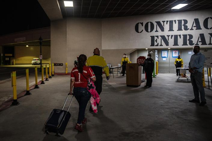 Maria Ana Mendez, left, enters the San Diego Convention Center to pick up her daughter on April 7, 2021. (Ariana Drehsler for The New York Times)