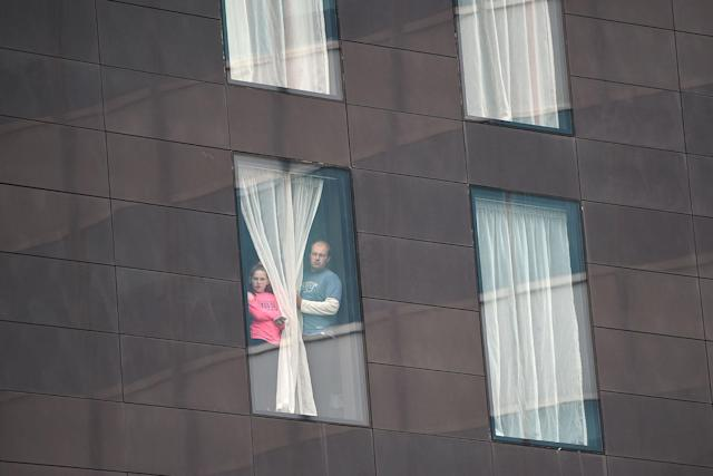<p>People affected by the deadly terror attack at Manchester Arena look out from a hotel window in Manchester, northwest England on May 23, 2017. (Oli Scarff/AFP/Getty Images) </p>