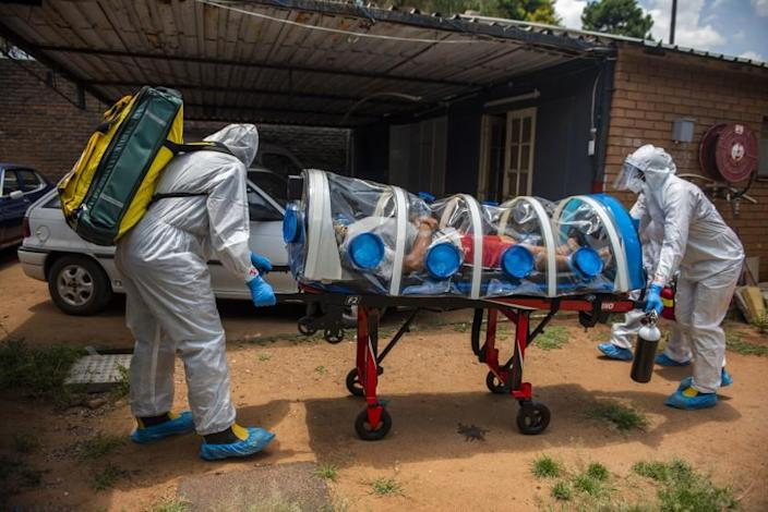 PRETORIA, SOUTH AFRICA - JANUARY 15: Members of the Tshwane Special Infectious Unit on COVID-19 wearing personal protective equipment (PPE) pick up a suspected COVID-19 patient on January 15, 2021 in Pretoria, South Africa. The Special Infectious Unit ambulance is equipped with an isolation chamber with a negative pressure filtration system. (Photo by Alet Pretorius/Gallo Images via Getty Images)