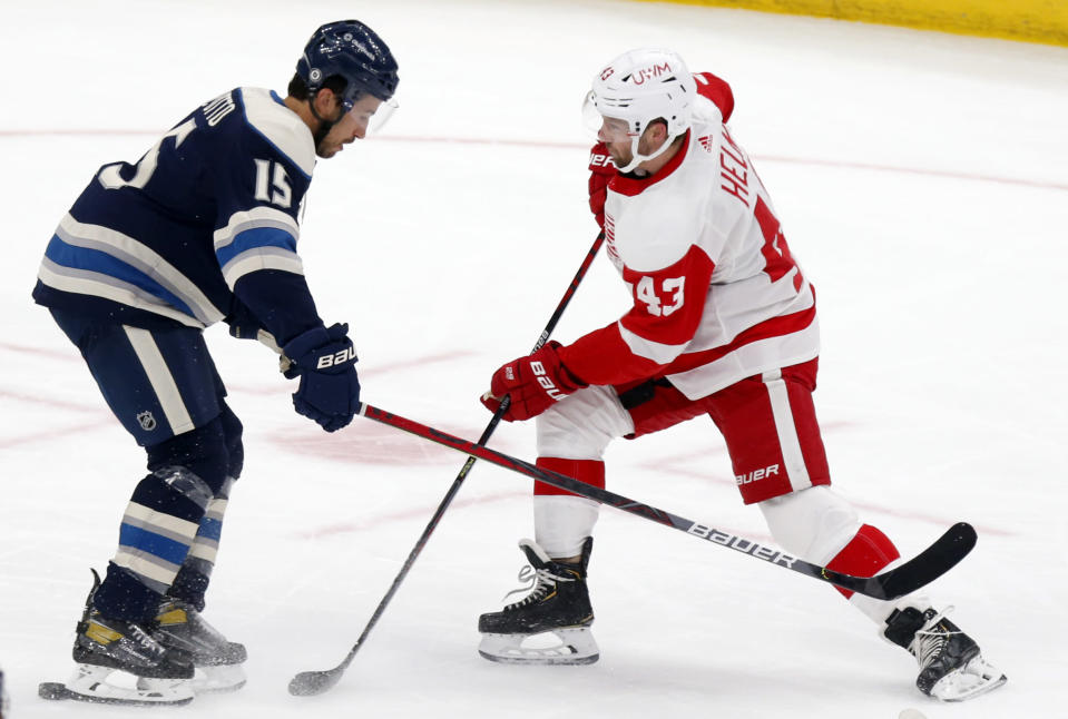 Detroit Red Wings forward Darren Helm, right, works against Columbus Blue Jackets defenseman Michael Del Zotto during the first period of an NHL hockey game in Columbus, Ohio, Friday, May 7, 2021. (AP Photo/Paul Vernon)