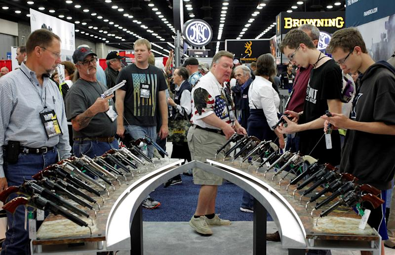 Gun enthusiasts look over Benelli USA guns at a National Rifle Association show in Louisville, Kentucky, May 21, 2016.