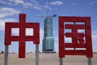"""The Shenzhou-12 spacecraft sits covered on a launch pad near Chinese characters for """"China"""" at the Jiuquan Satellite Launch Center near Jiuquan, China on Wednesday, June 16, 2021. China plans to launch three astronauts onboard the Shenzhou-12 spacecraft, who will be the first crew members to live on China's new orbiting space station Tianhe, or Heavenly Harmony, from the Jiuquan Satellite Launch Center in northwest China. (AP Photo/Ng Han Guan)"""