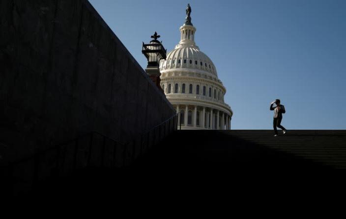 FILE PHOTO: A visitor walks outside of the U.S. Capitol before an expected House vote on appointing impeachment managers in Washington