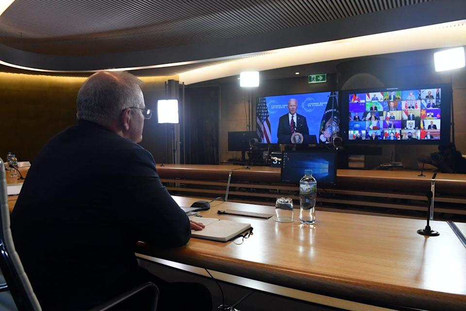 Man at desk looks at two TV screens