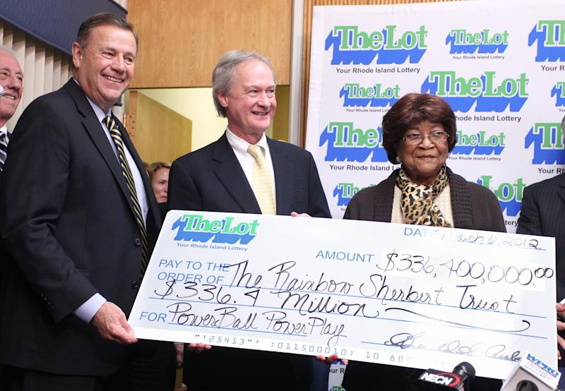 Louise White, right, 81 from Newport, R.I., is presented a check for $336 million by Gerald Aubin, left, director of the state's lottery, and Gov. Lincoln Chafee, center, at Rhode Island Lottery headquarters in Cranston, R.I., Tuesday, March 6, 2012. White won last month's $336.4 million Powerball jackpot, sleeping with the winning ticket in her Bible until coming forward to claim the sixth-largest U.S. prize on Tuesday, a family representative said.  (AP Photo/Stew Milne)