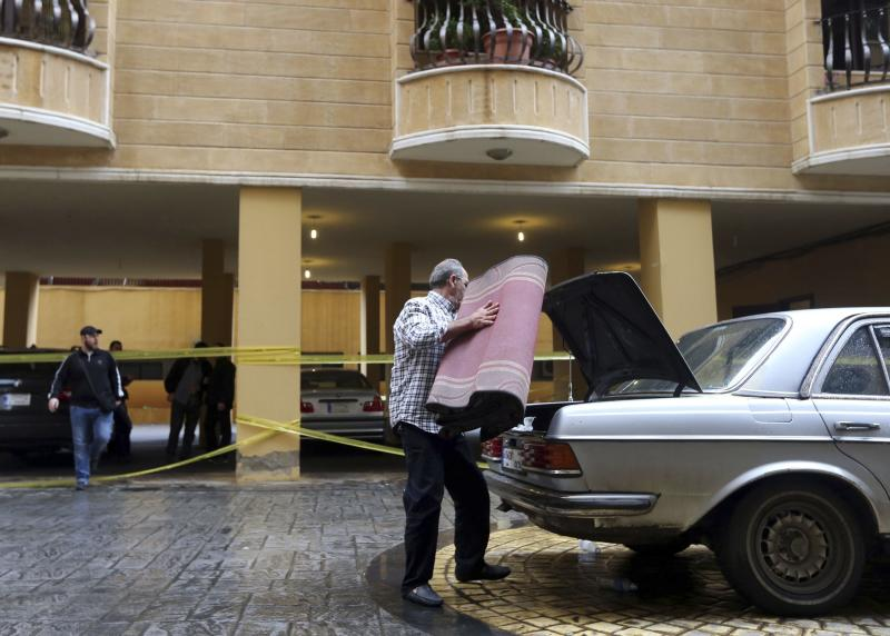 A man puts a carpet on the back of a car near the crime scene where commander Hasan al-Laqqis was killed in the southern Hadath district in Beirut December 4, 2013. Lebanon's Shi'ite militant Hezbollah group said on Wednesday al-Laqis was killed outside his Beirut home in an overnight attack it blamed on Israel. Israel denied any role in the killing, which Hezbollah said took place at around midnight in the southern Hadath district of the Lebanese capital. REUTERS/Hasan Shaaban (LEBANON - Tags: POLITICS CIVIL UNREST)
