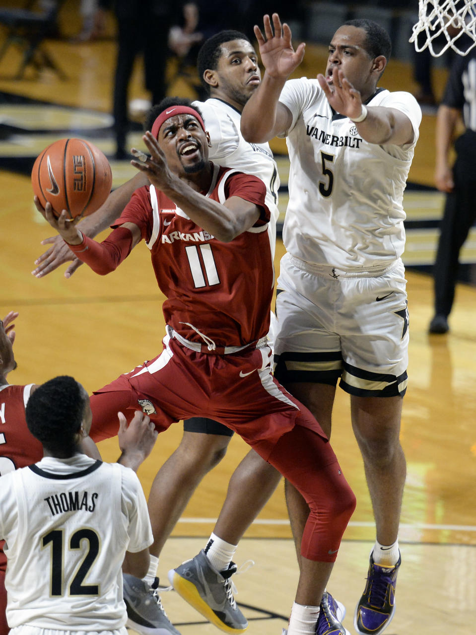 Arkansas guard Jalen Tate (11) shoots against Vanderbilt guard D.J. Harvey (5) during the second half of an NCAA college basketball game against Vanderbilt Saturday, Jan. 23, 2021, in Nashville, Tenn. Arkansas won 92-71. (AP Photo/Mark Zaleski)