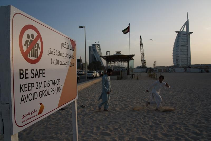 File - In this Friday, March 20, 2020 file photo, two laborers play tag near a sign warning people to maintain a distance from each other over the outbreak of the new coronavirus in front of the sail-shaped Burj Al Arab luxury hotel in Dubai, United Arab Emirates. The United Arab Emirates has closed its borders to foreigners, including those with residency visas, over the coronavirus outbreak, but has yet to shut down public beaches and other locations over the virus. (AP Photo/Jon Gambrell, File)