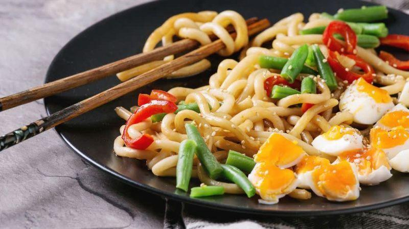 Plate of sesame udon noodles with chopsticks