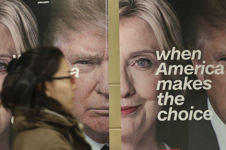 A woman walks by banners of Democratic presidential candidate Hillary Clinton and Republican presidential candidate Donald Trump during an election watch event hosted by the U.S. Embassy in Seoul, South Korea, Nov. 9, 2016. (Photo: Lee Jin-man/AP)
