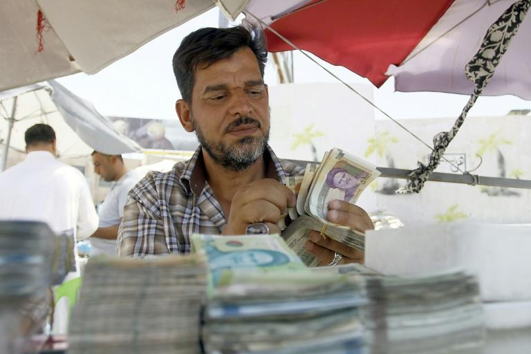 An Iraqi vendor sells Iranian currency on a street in Najaf on August 14, 2018