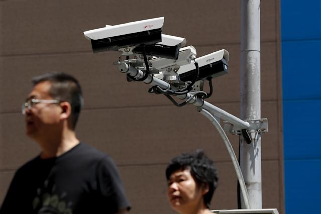 People walk by Chinese-made surveillance cameras installed along a street in Beijing, Thursday, May 23, 2019. The Chinese video surveillance company Hikvision says it is taking concern about the use of its technology seriously following a report that the U.S. may block several Chinese surveillance companies from buying American components. (AP Photo/Andy Wong)