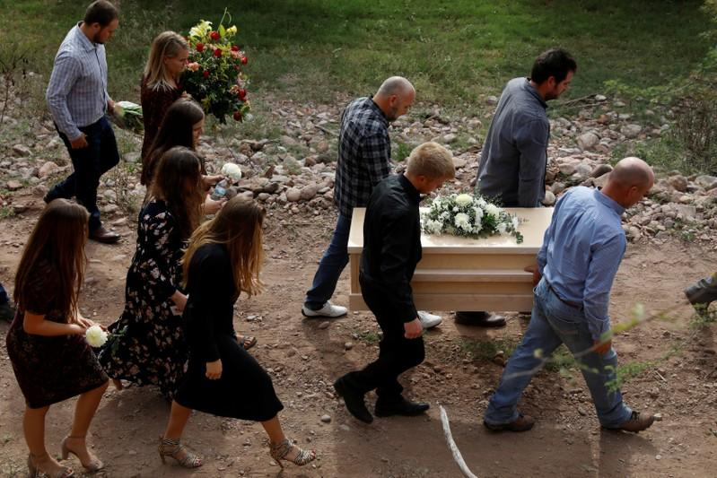 Men carry the remains of Dawna Ray Langford and her sons Trevor and Rogan, who were killed by unknown assailants, to be buried at the cemetery in La Mora