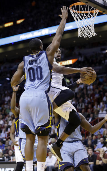 Miami Heat's Dwyane Wade, center, goes to the basket against Memphis Grizzlies' Darrell Arthur (00) in the first half of an NBA basketball game in Miami, Friday, March 1, 2013. (AP Photo/Alan Diaz)