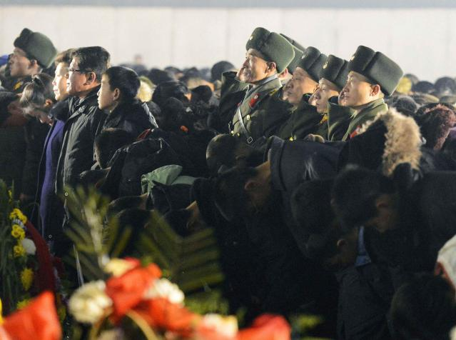 North Korean soldiers salute as civilians bow to bronze statues of North Korea's late founder Kim Il Sung and late leader Kim Jong Il at Mansudae in Pyongyang