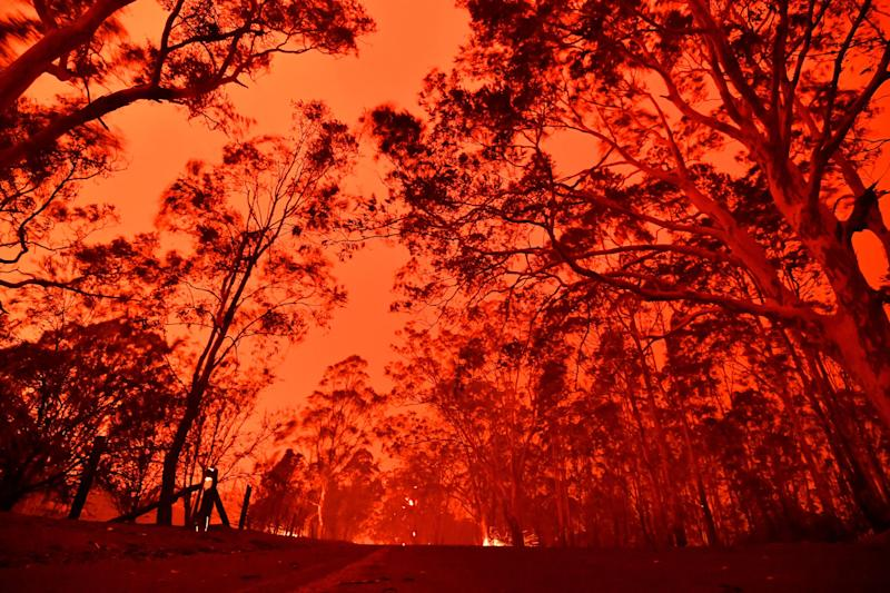TOPSHOT - The afternoon sky glows red from bushfires in the area around the town of Nowra in the Australian state of New South Wales on December 31, 2019. - Thousands of holidaymakers and locals were forced to flee to beaches in fire-ravaged southeast Australia on December 31, as blazes ripped through popular tourist areas leaving no escape by land. (Photo by SAEED KHAN / AFP) (Photo by SAEED KHAN/AFP via Getty Images)