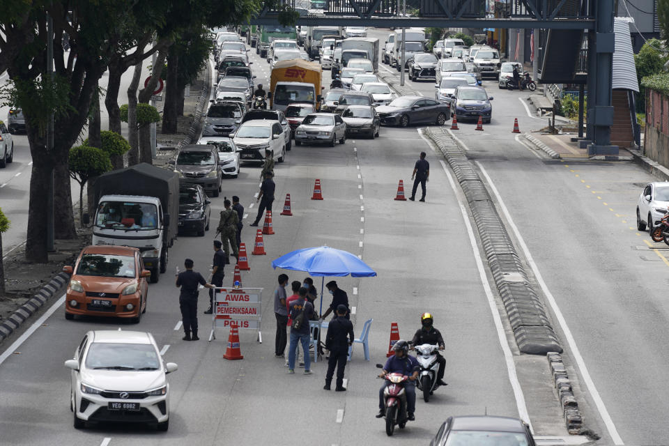 Police officers check vehicles at a roadblock to ensure that people abide by a movement control order in downtown Kuala Lumpur, Malaysia, Wednesday, Oct. 14, 2020. Malaysia will restrict movements in its biggest city Kuala Lumpur, neighboring Selangor state and the administrative capital of Putrajaya from Wednesday to curb a sharp rise in coronavirus cases. (AP Photo/Vincent Thian)