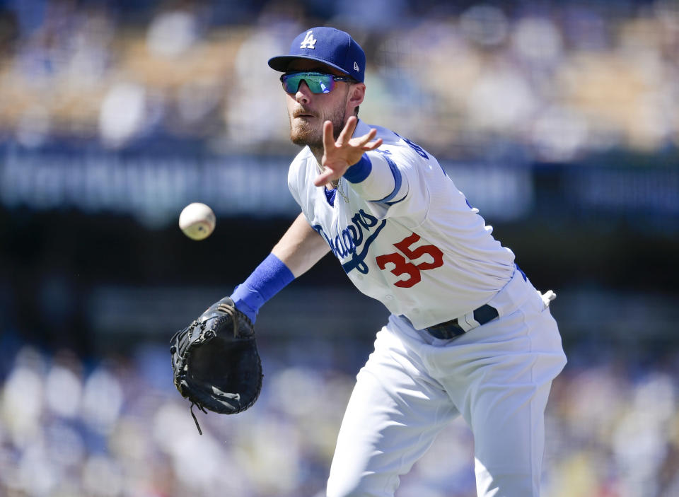 Los Angeles Dodgers first baseman Cody Bellinger tosses the ball to first base to force out San Francisco Giants' Kevin Pillar on a bunt-attempt during the fourth inning of a baseball game in Los Angeles, Sunday, Sept. 8, 2019. (AP Photo/Kelvin Kuo)