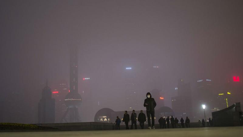 A man wearing an air mask walks through downtown Shanghai, China. The sky is filled with smog.