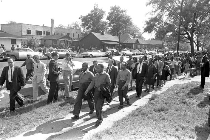 """FILE - Rev. Ralph Abernathy, left, and Rev. Martin Luther King Jr. lead a column of demonstrators as they attempt to march on Birmingham, Ala., city hall April 12, 1963. Police intercepted the group short of their goal. Rev. Jonathan McPherson, shown in a coat and tie two people behind King, in 2021 is urging protesters against racial injustice to """"keep on keeping on."""" (AP Photo/Horace Cort)"""