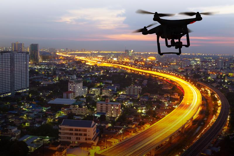 A drone hovers over a city at sunset.