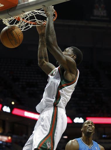 Milwaukee Bucks' Larry Sanders, left, dunks the ball as Orlando Magic's Dwight Howard, right, watches during the second half of an NBA basketball game, Monday, Feb. 20, 2012, in Milwaukee. (AP Photo/Jeffrey Phelps)