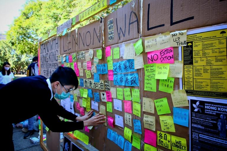"""A supporter of the Hong Kong pro-democracy protests sticks a note on a makeshift """"Lennon Wall"""" at the University of Queensland in Brisbane (AFP Photo/Patrick HAMILTON)"""