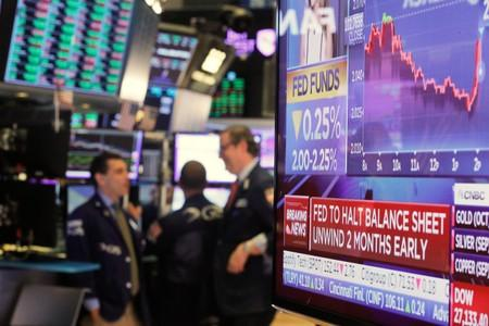 A screen displays the U.S. Federal Reserve interest rates announcement as traders work on the floor of the New York Stock Exchange (NYSE) in New York