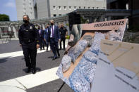 Officials walk past images of illegal drugs outside the Edward R. Roybal Federal Building, Thursday, May 13, 2021, in Los Angeles. Federal authorities say they have arrested at least 10 suspected drug dealers accused of selling fentanyl and other opioids that led to overdose deaths. (AP Photo/Marcio Jose Sanchez)