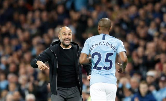 Guardiola (left) is confident Fernandinho will stay at the Etihad beyond his current deal (Martin Rickett/PA)