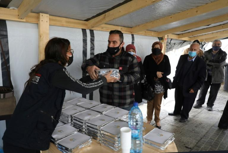 A volunteer gives out food to people in need at the Lebanese Grassroots organisation in Beirut's Mar Mikhael district, which was hard hit by last year's devastating port explosion