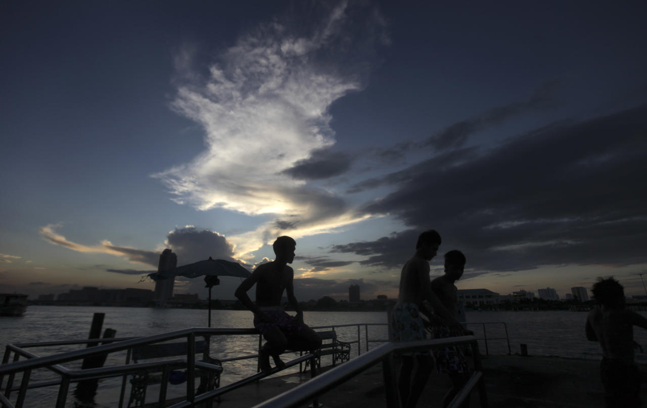 Thai boys are silhouetted as they sit on a jetty on the bank of the swollen Chao Phraya River in Bangkok, Thailand, Saturday, Oct. 29, 2011. Defenses shielding the center of Thailand's capital from the worst floods in nearly 60 years mostly held at critical peak tides Saturday, but areas along the city's outskirts remained submerged along with much of the countryside. (AP Photo/Altaf Qadri)