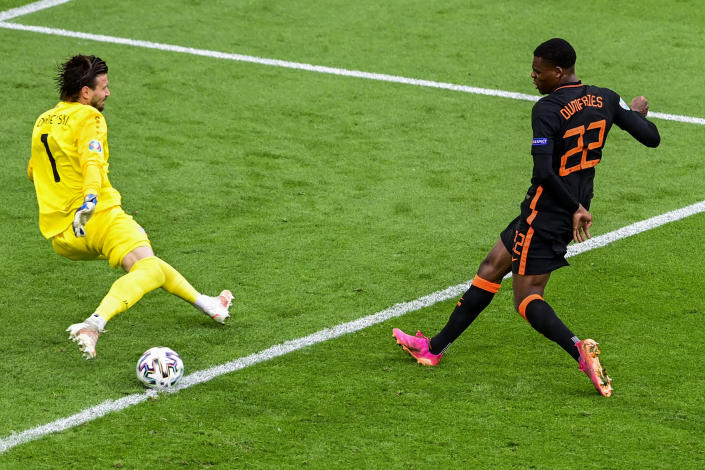 CORRECTS PHOTOGRAPHER NAME - Denzel Dumfries of the Netherlands, right, kicks the ball next to North Macedonia's goalkeeper Stole Dimitrievski during the Euro 2020 soccer championship group C match between North Macedonia and The Netherlands at the Johan Cruyff ArenA in Amsterdam, Netherlands, Monday, June 21, 2021. (Olaf Kraak, Pool via AP)