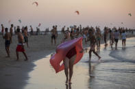 People enjoy the day on the beach, in Tel Aviv, Israel, Sunday, Oct 18, 2020. Movement limitations were lifted and some businesses reopened Sunday as Israel relaxed some restrictions imposed during a month long nationwide lockdown. (AP Photo/Oded Balilty)
