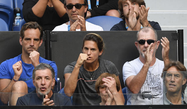 Amelie Mauresmo, center, coach of France's Lucas Pouille, watches from the players box during his quarterfinal match against Canada's Milos Raonic at the Australian Open tennis championships in Melbourne, Australia, Wednesday, Jan. 23, 2019. (AP Photo/Andy Brownbill)