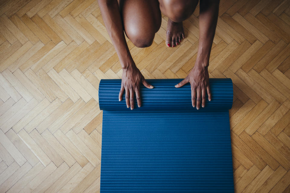 From above photo of unrecognizable African-American woman folding fitness mat before or after working out at home