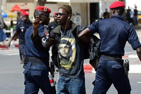 Police officers detain a demonstrator during a protest  in Dakar