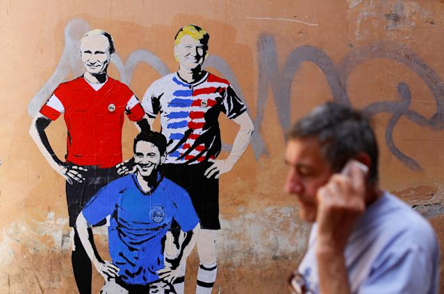 "<p>A man walks past a mural signed by ""TV Boy"" and depicting Russian President Vladimir Putin, U.S. President Donald Trump and Italian Prime Minister Giuseppe Conte as soccer players in downtown Rome, Italy June 15, 2018. (Photo: Tony Gentile/Reuters) </p>"