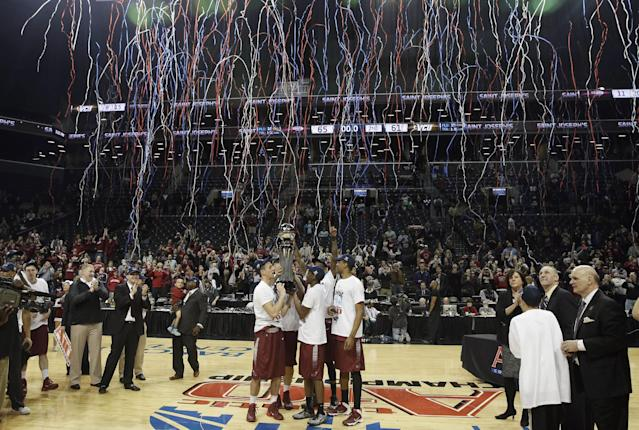 FILE - In this March 16, 2014, file photo, members of the Saint Joseph's team hold the championship trophy after an NCAA college basketball game against VCU in the championship round of the Atlantic 10 Conference tournament at the Barclays Center in New York. The Atlantic 10 was scheduled to play its tournament there through 2017, but will move in exchange for playing an ACC/A-10 doubleheader at Barclays during the 2015-16, 2016-17 and 2017-18 seasons. The A-10 tournament will then return to Barclays for three years starting in 2019. (AP Photo/Seth Wenig, File)