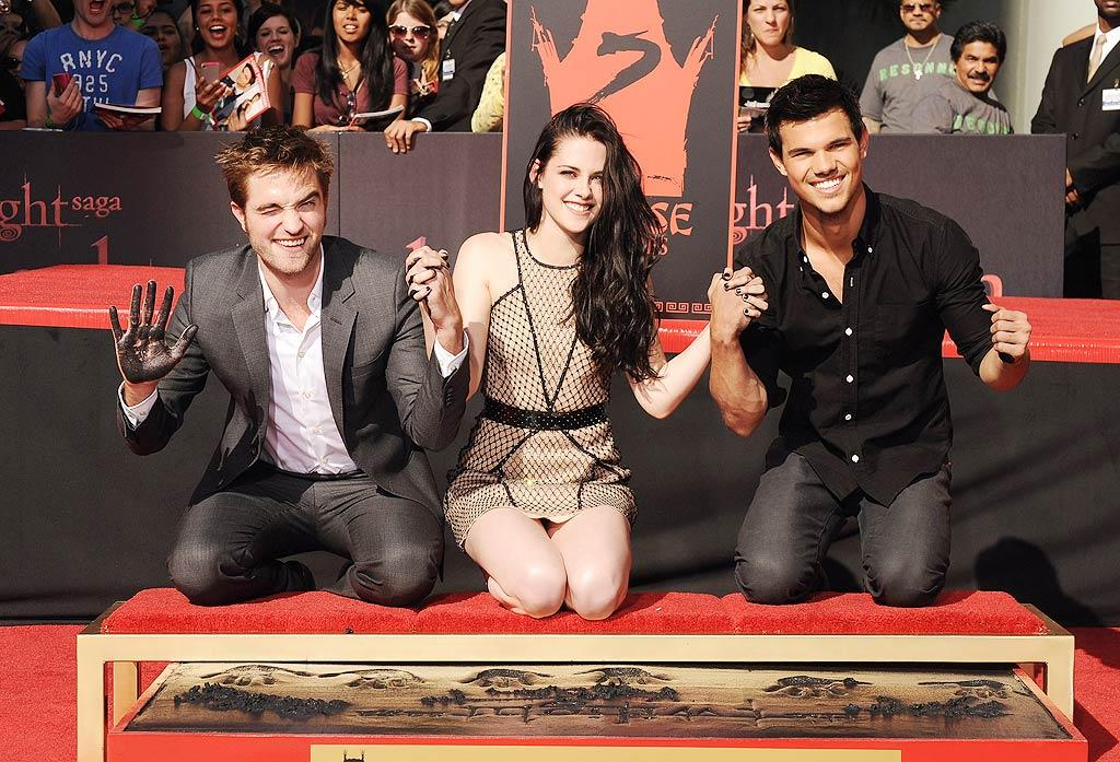 """Thousands of """"Twilight"""" fans lined up on Thursday to get a glimpse of the film franchise's heartthrobs (L-R) Robert Pattinson, Kristen Stewart, and Taylor Lautner. The three became part of Hollywood Boulevard forever at their Hand and Footprint Ceremony at the fabled Grauman's Chinese Theatre. (11/3/2011)"""