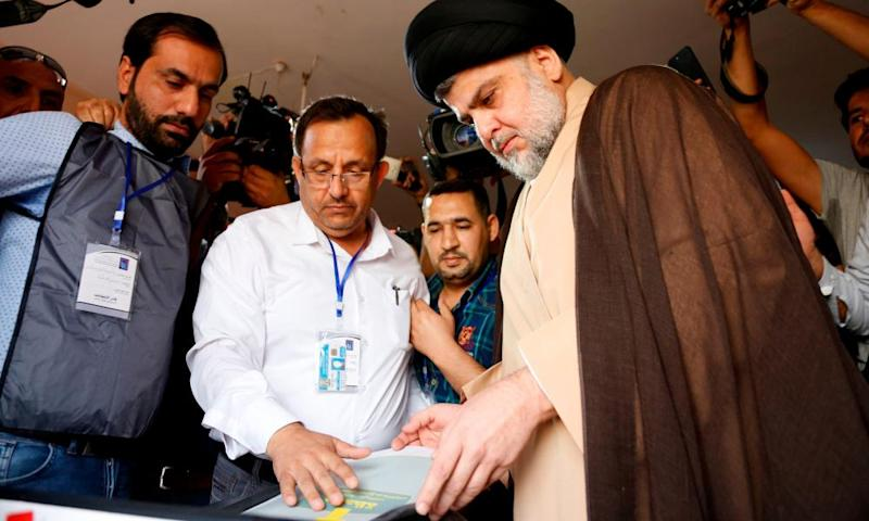 Iraqi Shia cleric Moqtada al-Sadr, right, casts his vote at a polling station in Najaf