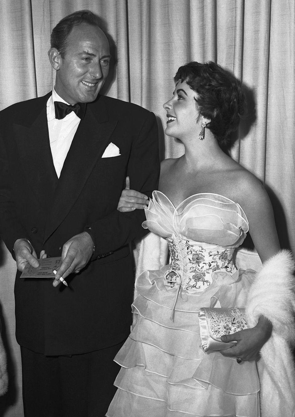 <p>Liz dropped jaws in this tiered strapless gown featuring a corset lace-up bodice. She complemented it with drop earrings and a coordinating satin clutch. She posed with her husband Michael Wilding, whom she married the previous year.</p>