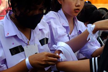 Students tie symbolic white ribbons showing their support for restoring democracy. Photo: Krittin Kitsahawong