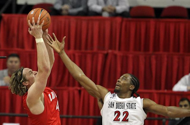 New Mexico's Cameron Bairstow, left, and San Diego State's Josh Davis try to bring down a rebound during the first half of an NCAA college basketball game for the Mountain West Conference tournament championship on Saturday, March 15, 2014, in Las Vegas. (AP Photo/Isaac Brekken)