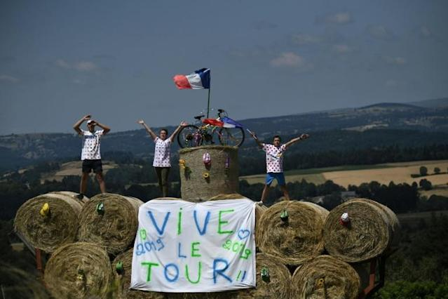 "Cycling enthusiasts wearing polka dot jerseys wave as they stand on a stack of haybales with a message reading ""Long live the Tour"" during the tenth stage of the 106th edition of the Tour de France cycling race (AFP Photo/JEFF PACHOUD)"