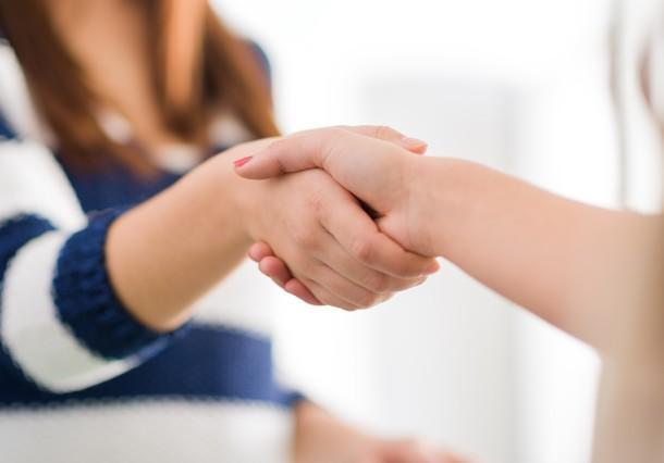 Close-up of two people shaking hands after resolution of a dispute