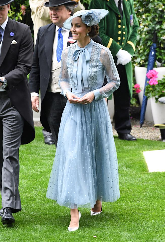 The Duchess of Cambridge debuted a new powder blue Elie Saab ensemble with sheer sleeves and pussy-bow detailing for day one of Royal Ascot with a Philip Treacy floral hat, metallic heels and her Kiki McDonough topaz earrings. [Photo: PA]